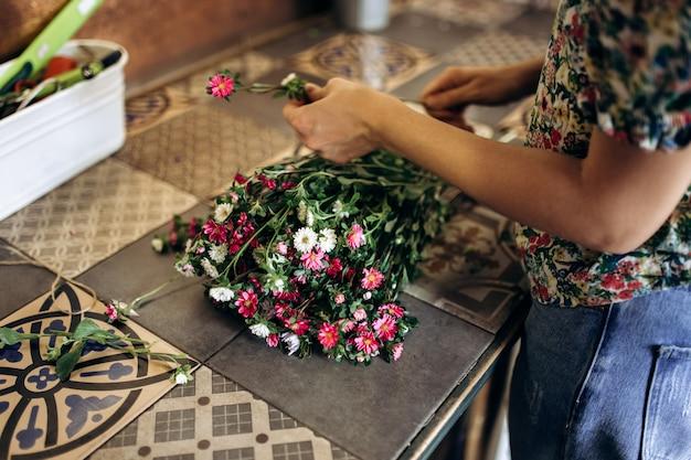 꽃집은 신선한 흰색과 분홍색 국화 꽃다발을 수집하고 있습니다.