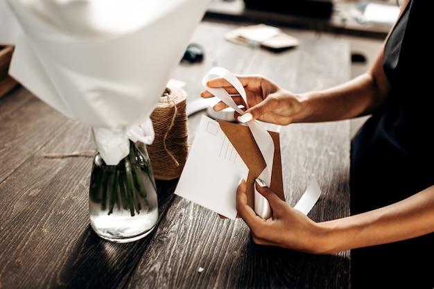 Флорист упаковывает открытку в конверт с белой лентой на деревянном столе.