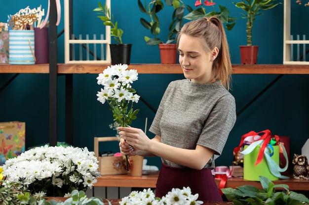 플로리스트가 꽃다발을 만듭니다. 젊은 성인 소녀가 꽃다발을 위해 흰 국화를 선택합니다.