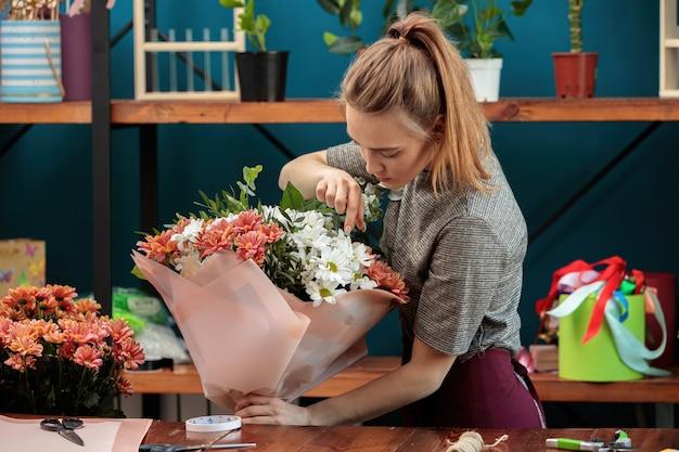 Флорист составляет букет. юная взрослая девушка держит в руках большой букет разноцветных хризантем и проверяет его.