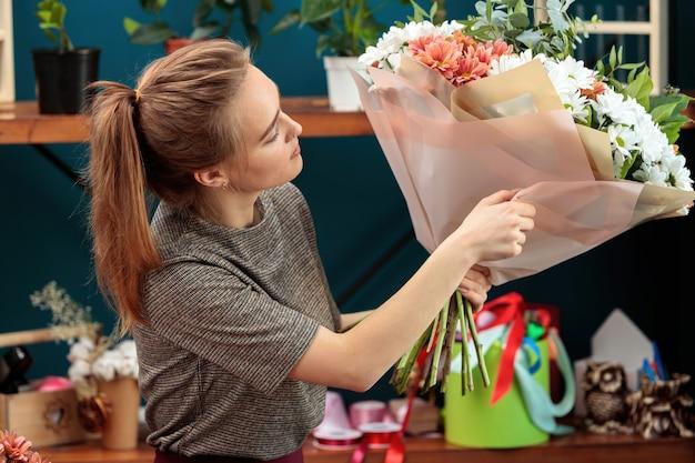 꽃집은 꽃다발을 만듭니다. 젊은 성인 소녀가 손에 커다란 국화 꽃다발을 들고 확인합니다.