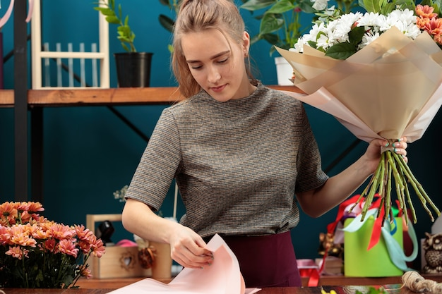 Флорист составляет букет. юная взрослая девушка держит в руках большой букет разноцветных хризантем и выбирает бумагу для украшения.