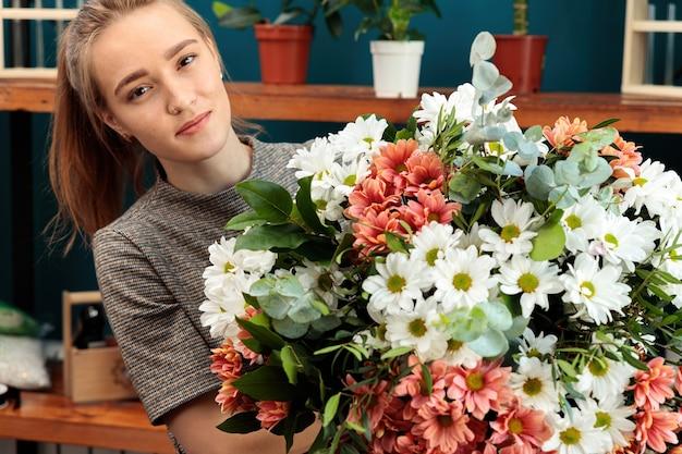 꽃집은 꽃다발을 만듭니다. 한 젊은 성인 소녀가 손에 커다란 국화 꽃다발을 들고 카메라를 바라보고 있습니다.