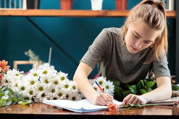 플로리스트가 꽃다발을 만듭니다. 젊은 성인 소녀는 노트북에 주문을 씁니다.