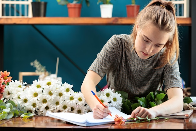 꽃집은 꽃다발을 만듭니다. 젊은 성인 소녀가 공책에 주문을 씁니다.