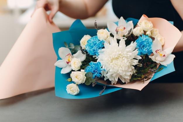 Флорист делает букет в цветочном бутике