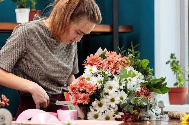 플로리스트는 국화 꽃다발을 만듭니다. 젊은 성인 여자가 위 장식 리본을 잘라냅니다.