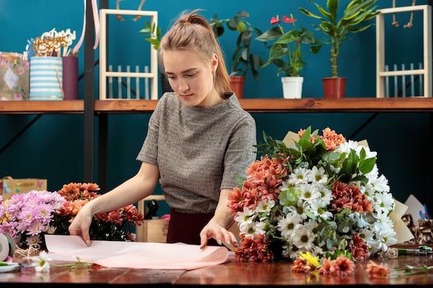 꽃집은 국화 꽃다발을 만듭니다. 젊은 성인 소녀는 장식용 종이를 선택합니다.
