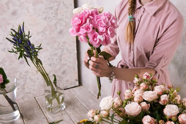 花屋は温室の花の花束を作ります。デコレータはピンクの花束のある温室で動作します。フロリスティックワークショップ、スキル、装飾、中小企業のコンセプト