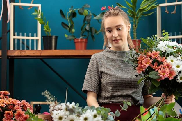 꽃집은 여러 가지 빛깔의 국화 꽃다발을 만듭니다. 젊은 성인 소녀는 꽃다발을 손에 들고 나머지 꽃을 어리둥절하게 봅니다.