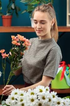 花屋は色とりどりの菊の花束を作ります。若い大人の女の子は彼女の手にいくつかの花を持って、それらを見ています。