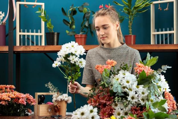 플로리스트는 여러 가지 색의 국화 꽃다발을 만듭니다. 젊은 성인 소녀가 열정적으로 일합니다.