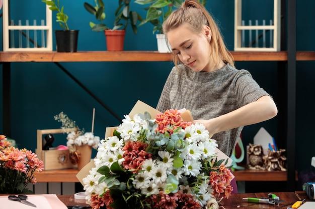 꽃집은 여러 가지 빛깔의 국화 꽃다발을 만듭니다. 젊은 성인 소녀는 열정적으로 일합니다.