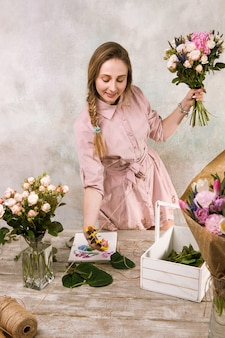 花屋は花屋でバラの花の花束を作ります。デコレータはピンクの花束のある温室で動作します。フロリスティックワークショップ、スキル、装飾、中小企業のコンセプト