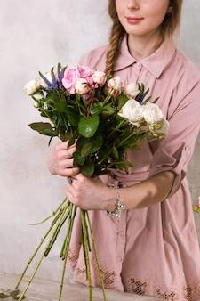 花屋はバラの花の花束を作ります。デコレータはピンクの花束のある温室で動作します。フロリスティックワークショップ、スキル、装飾、中小企業のコンセプト