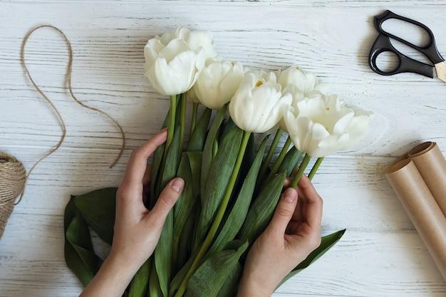 플로리스트는 흰색 튤립 꽃다발을 만듭니다.