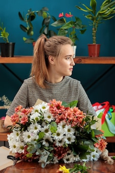 Florist makes a bouquet of multi-colored chrysanthemums. a young adult girl looks to the side.