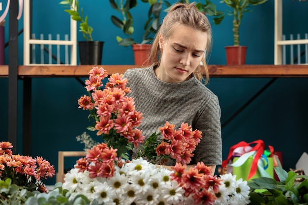 Florist makes a bouquet of multi-colored chrysanthemums. a young adult girl with a frown chooses flowers.