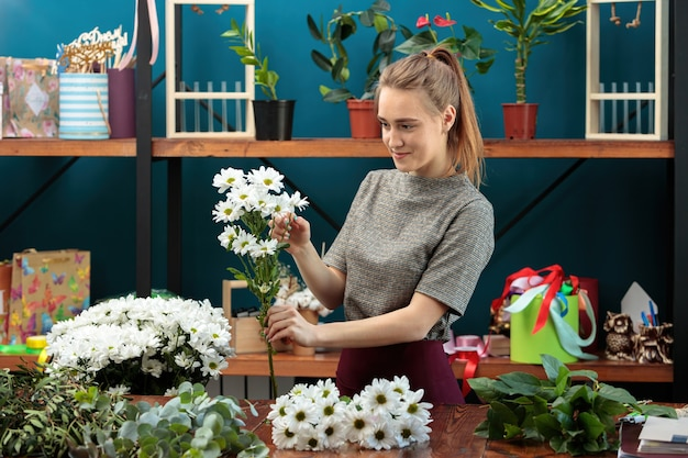 Florist makes a bouquet. a young adult girl chooses white chrysanthemums for a bouquet.