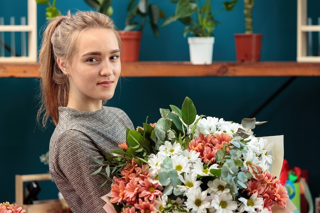 Florist makes a bouquet. a young adult girl holds a large bouquet of multi-colored chrysanthemums in her hands