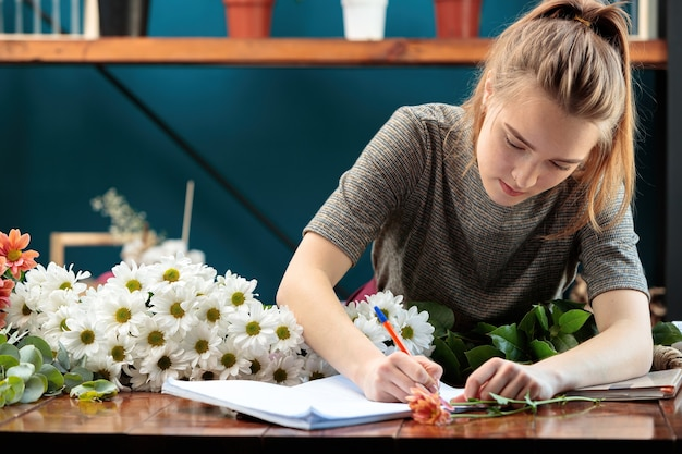 Florist makes a bouquet. a young adult girl writes an order in a notebook.