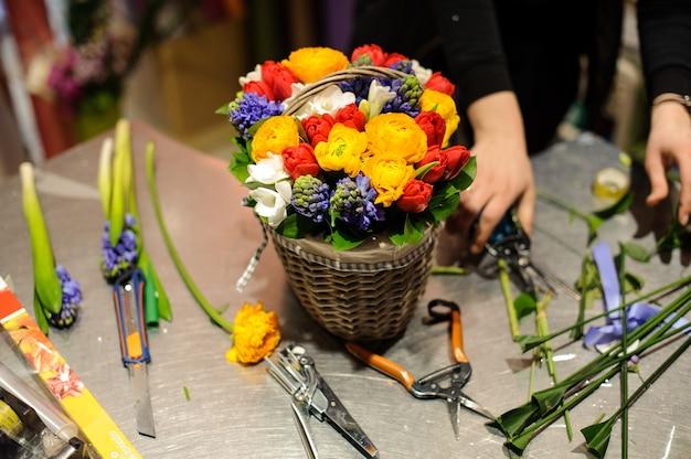 Флорист делает красивую цветочную композицию в плетеной корзине