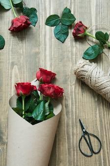 木製のテーブルにクラフト紙で包む赤いバラの花束を作る花屋