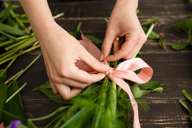 Флорист делает букет цветов, застегивает ленточку