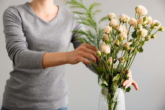 Флорист делает букет цветов в вазе