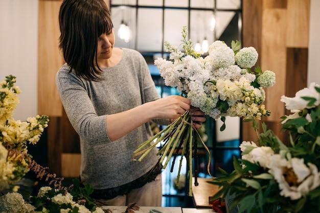 Флорист делает букет в цветочном магазине