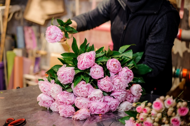 Florist making a bouquet of pink peonies