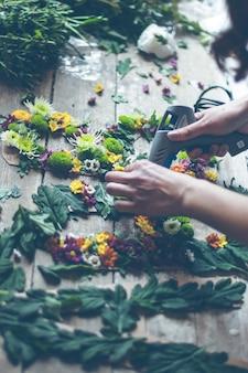 Флорист делает цветочное украшение буквами и клеем. снимок в помещении с естественным освещением и небольшой глубиной резкости