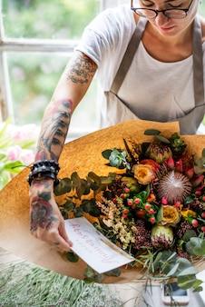 Florist making fresh flowers arrangement bouquet with happy anniversary card