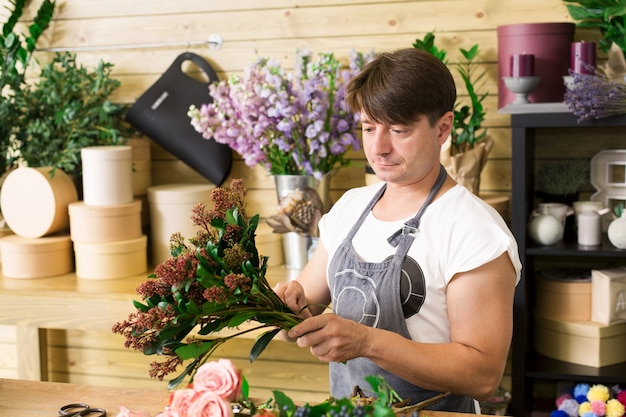 Florist making rose bouquet in flower shop. man assistant or owner in floral shop, making decorations and arrangements. flowers delivery, creating order