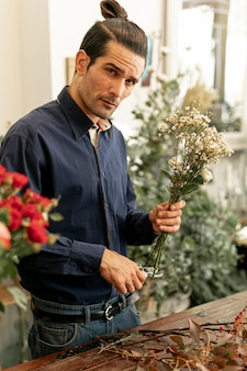 Florist male in shirt cutting flower stalks