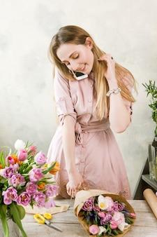 플로리스트 팩 축제 꽃다발과 전화로 이야기하십시오. 젊은 아름다운 꽃집은 꽃집이 나무 배경에 워크샵에서 분홍색 모란과 야생화로 조립하게합니다.