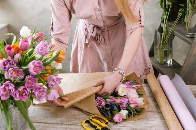 포장지에 플로리스트 팩 축제 꽃다발입니다. 젊은 아름 다운 꽃집 소녀 플로리스트는 나무 배경에 워크샵에서 분홍색 모란과 야생화와 조립합니다. 직장에서 여자의 손