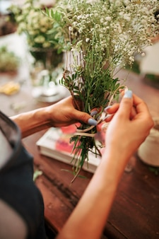 Florist's hand tying bunch of white flowers with string