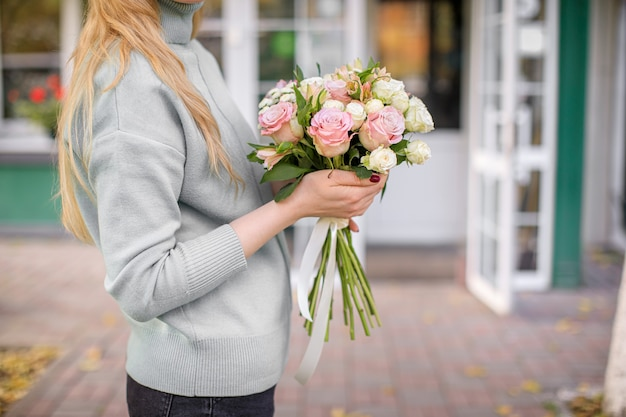 Florist shop in daylight. a woman holds a beautiful bouquet of flowers.