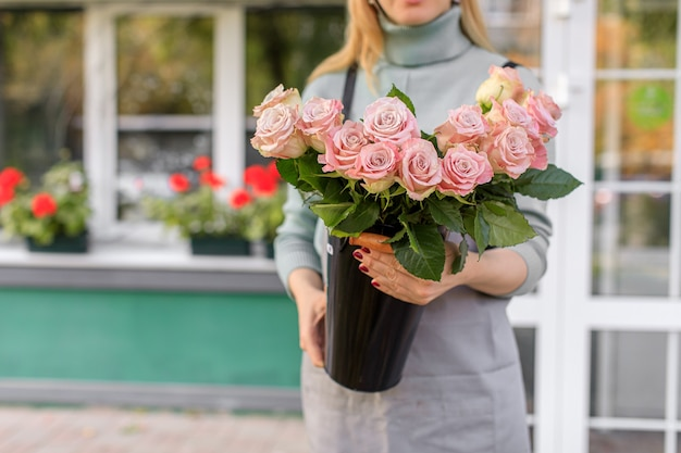 Florist shop in daylight. a woman holds a beautiful bouquet of flowers