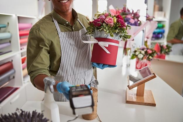손에 리본으로 감싼 냄비를 들고 고객에게 카드 스캔 기계를주는 플로리스트 샵 매니저