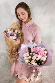 花屋はバラとチューリップの花の花束を示しています。デコレータはピンクの花束のある温室で動作します。フロリスティックワークショップ、スキル、装飾、中小企業のコンセプト
