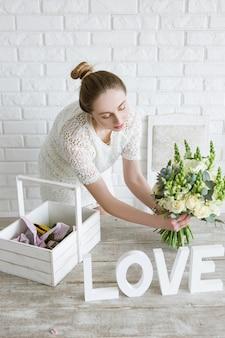 花屋はお店でフラワーブーケを披露します。若い女の子は、ワークショップで白い花のブライダル束を購入することを提案します。背景にレンガの壁があるライトデコレータスタジオ。