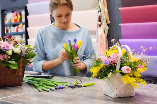 The florist takes care of bouquet.