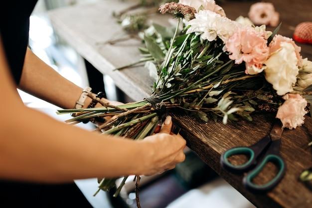 꽃집은 꽃집에서 꽃 줄기에 리본을 묶습니다.