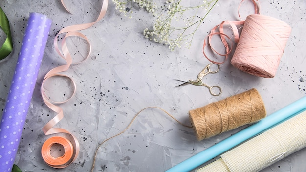 Florist tools and workplace with ribbons, flowers and scissors