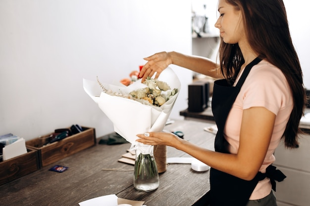 Florist touches bouquet of flowers in pastel colors packed in white paper is in a vase. .