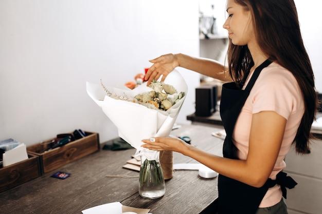 꽃집은 흰색 종이에 포장된 파스텔 색상의 꽃다발을 만지고 꽃병에 있습니다. .