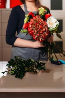 花の美しい花束を持つ花屋