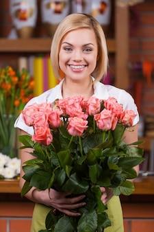Флорист с букетом роз. красивая молодая женщина со светлыми волосами в фартуке, держа букет роз и улыбаясь